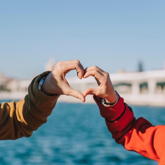 Crop Couple Montrant Le Coeur Avec Les Mains Photo gratuit