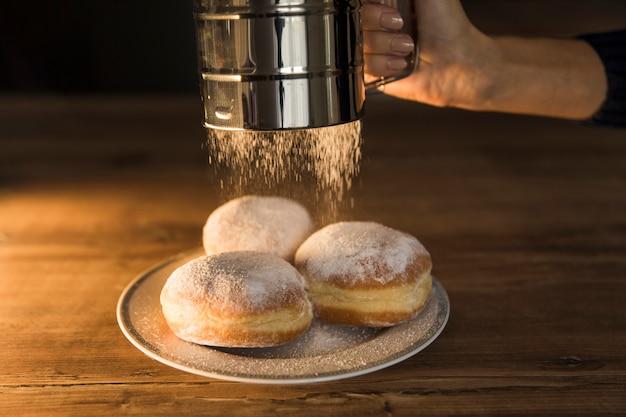 Crop hand renversant du sucre en poudre sur des beignets Photo gratuit