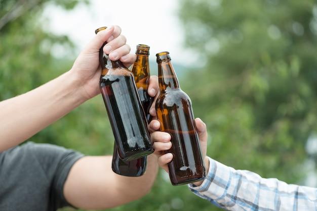 Crop hands tinter des bouteilles de bière dans la nature Photo gratuit