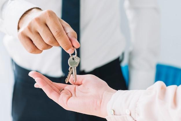 Crop immobilier agent donnant des clés à la femme Photo gratuit