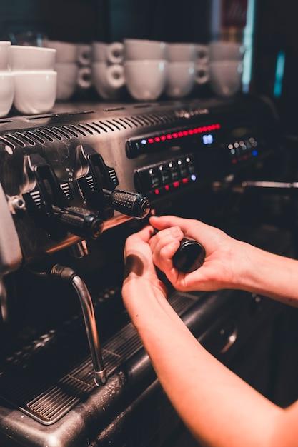 Crop main fixant portafilter à la machine à café Photo gratuit
