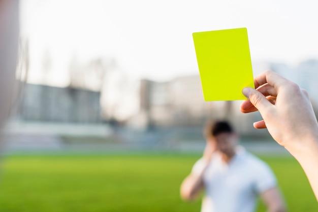 Crop main montrant le carton jaune Photo gratuit