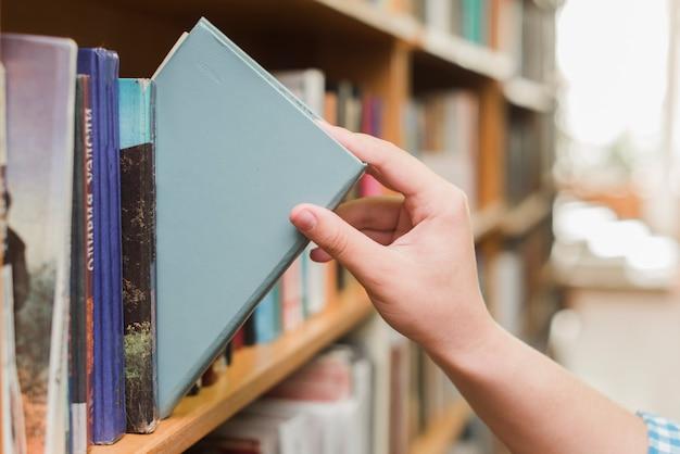 Crop main prenant le livre de l'étagère Photo gratuit