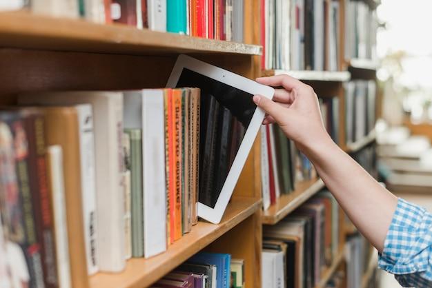 Crop Main Prenant La Tablette De La Bibliothèque Photo gratuit