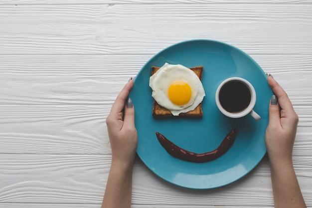 Crop mains tenant la plaque avec le petit déjeuner Photo gratuit