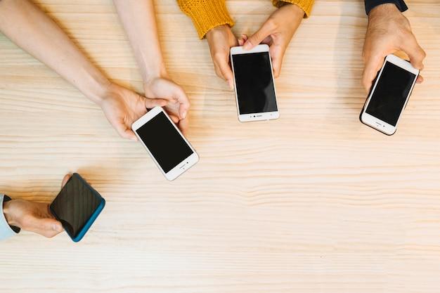Crop mains tenant et en utilisant des téléphones mobiles Photo gratuit