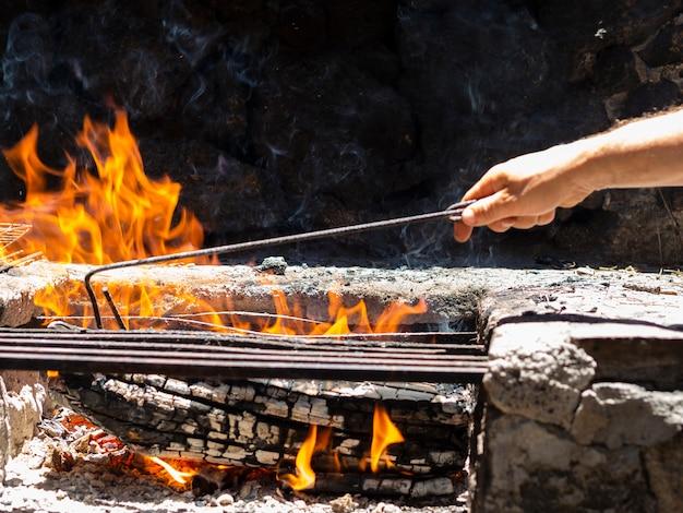 Crop man vérifiant les cendres dans un feu de joie Photo gratuit