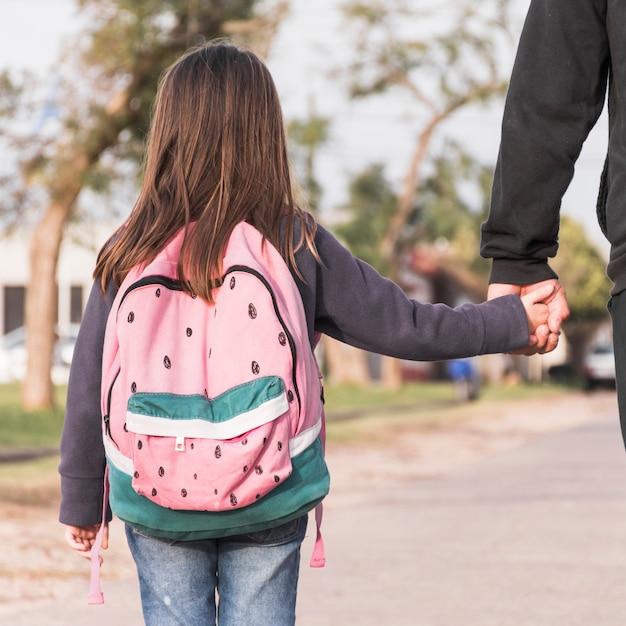 Crop parent marchant fille à l'école Photo gratuit