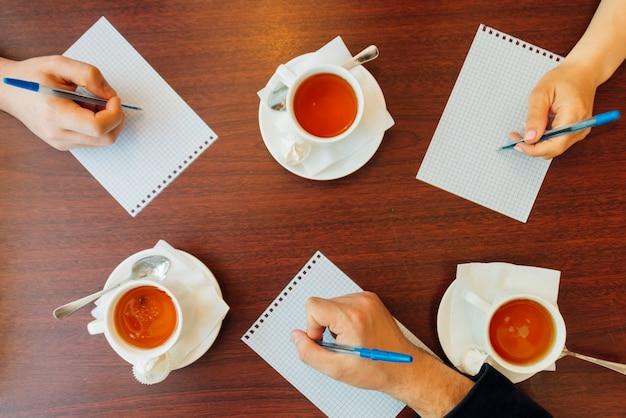Crop people écrit sur papier parmi des tasses à thé Photo gratuit