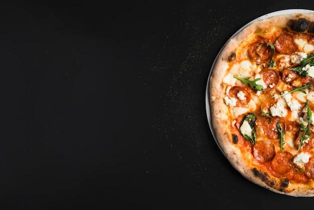 Crop pizza sur le noir Photo gratuit