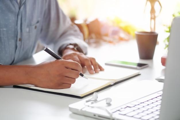 Cropped tourné un homme écrivant sur papier cahier sur le lieu de travail. Photo Premium