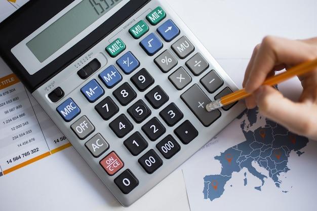 Cropped view of man hand travailler avec la calculatrice Photo gratuit