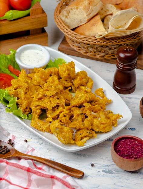 Croquettes de poulet servies avec sauce à la mayonnaise et au yogourt à l'intérieur d'une assiette blanche avec laitue et tomates Photo gratuit