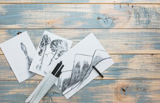 Croquis dessinés à la main créative et des bâtons de charbon de bois sur le bureau en bois Photo gratuit