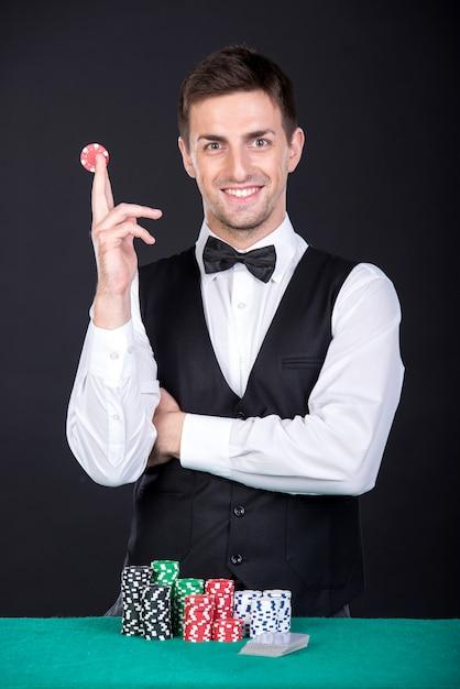 Croupier souriant avec des jetons de jeu sur la table verte. Photo Premium