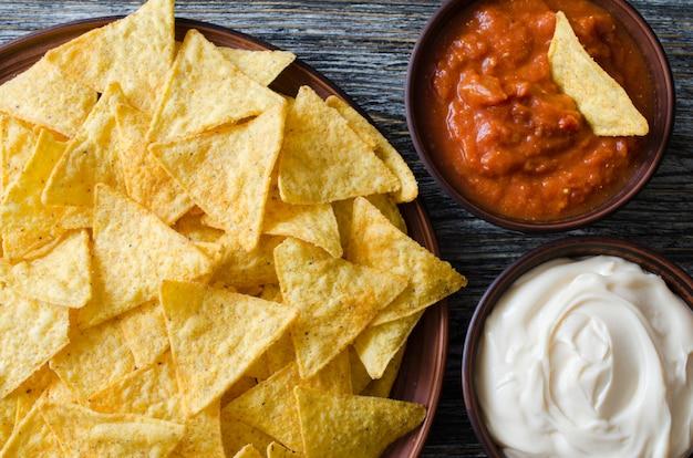 Croustilles de maïs nachos avec sauces épicées à la tomate et au fromage. Photo Premium