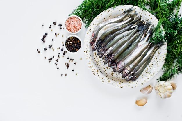 Le cru crue sur une assiette, l'aneth, le sel rose, le poivre et l'ail. Photo Premium