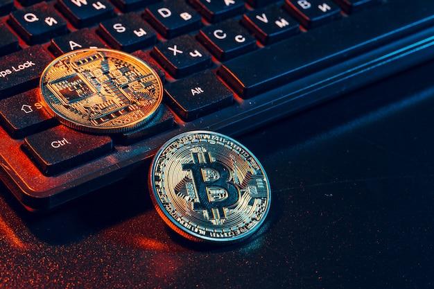 Cryptocurrency de pièce de bitcoin d'or sur le clavier d'ordinateur portable. Photo Premium