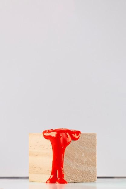 Cube en bois avec gouttes de peinture orange Photo gratuit