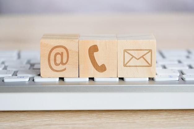Cube en bois avec les symboles d'image du courrier électronique, du téléphone et du courrier. contact pour la communication. Photo Premium