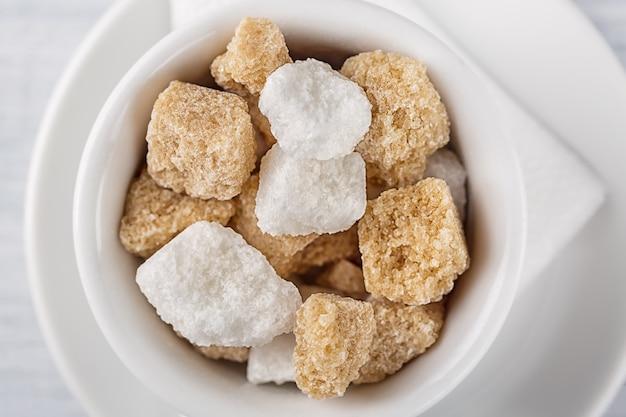 Cube de sucre blanc et de canne à sucre brun dans un bol blanc sur fond blanc. Photo Premium
