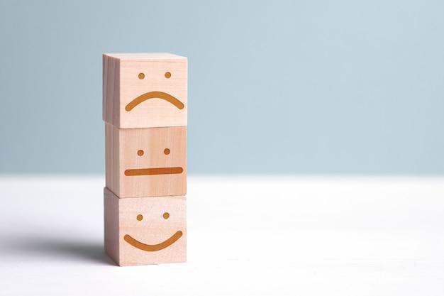 Cubes En Bois Avec L'image D'une Personne Positive à Côté Du Mécontent Et Du Neutre. Pour évaluer Une Action Ou Une Ressource. Photo Premium