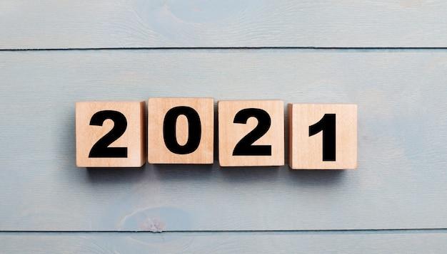 Cubes En Bois Avec Numéros 2021 Sur Un Fond En Bois Bleu Clair. Concept De Nouvel An Photo Premium