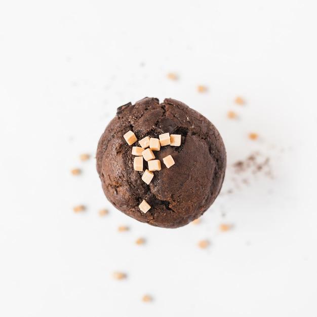 Cubes de bonbons au caramel sur cupcake marron sur fond blanc Photo gratuit