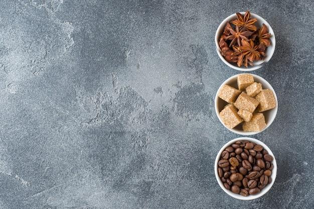 Cubes de cassonade, grains de café et anis étoilé sur béton. espace de copie Photo Premium