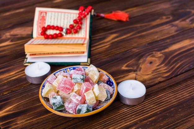 Cubes multicolores de rakhat-lukum dans une assiette avec un livre sacré islamique; chapelet et bougies sur le bureau en bois Photo gratuit