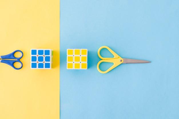 Les cubes de rubik et les ciseaux colorés Photo gratuit