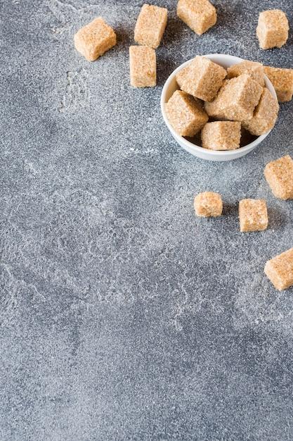 Cubes de sucre de canne brun sur béton. espace de copie Photo Premium