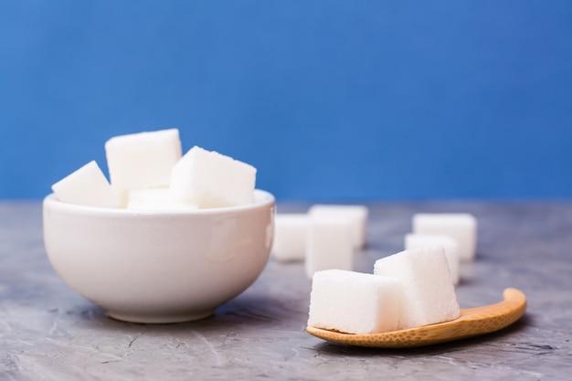 Cubes de sucre dans un bol blanc et une cuillère en bois sur une table sur un fond bleu Photo Premium
