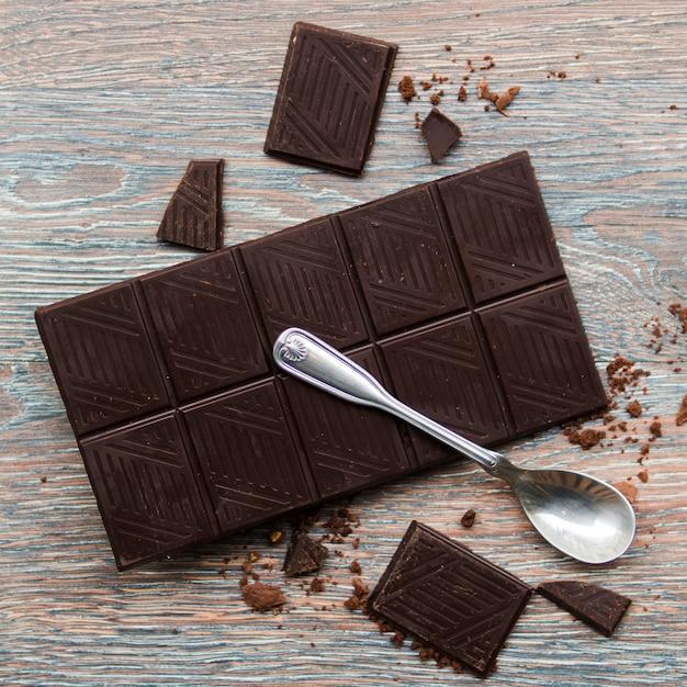 Cuillère et barre de chocolat noir Photo gratuit