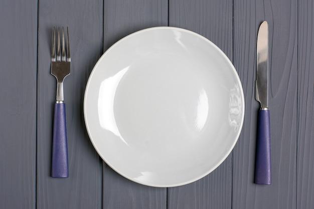 Cuillère bleu foncé, fourchette, couteau, assiette grise sur une table en bois grise Photo Premium