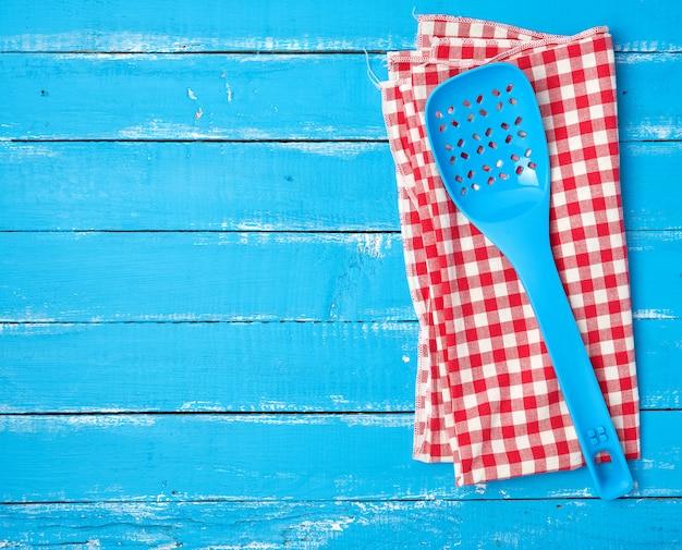 Cuillère bleue en plastique avec trous sur une serviette en tissu rouge Photo Premium