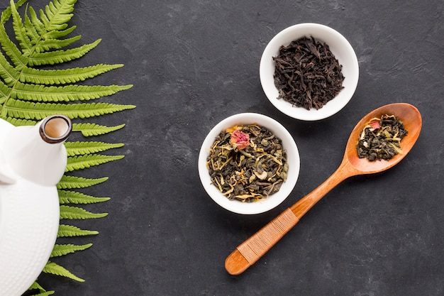 Cuillère en bois et bol en céramique d'herbe à thé sur une surface noire Photo gratuit