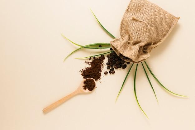 Cuillère en bois avec café moulu et sac Photo gratuit