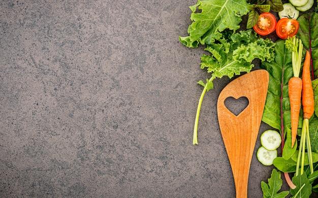 Cuillère En Bois Et Légumes Sur Fond De Pierre Sombre. Photo Premium