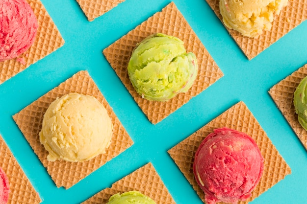 Cuillère à crème glacée aux fruits sur des gaufres carrées sur une surface turquoise Photo gratuit