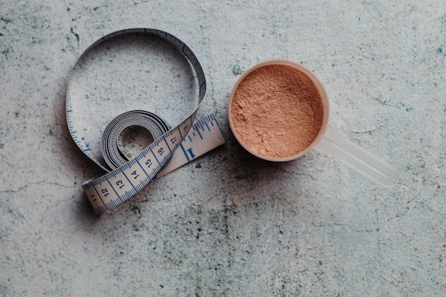 Une cuillère ou une cuillère de protéines de lactosérum à texture visible. saveur de chocolat. fond en béton Photo Premium
