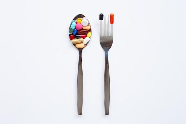 Cuillère et folk avec des comprimés colorés, des capsules et des pilules sur blanc Photo Premium
