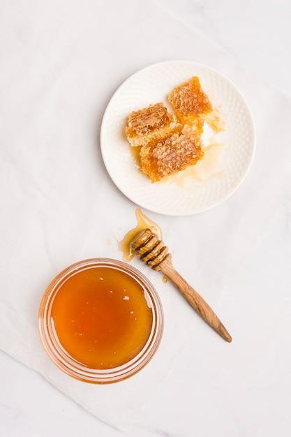 Cuillère à miel vue de dessus avec des morceaux de nid d'abeille Photo gratuit