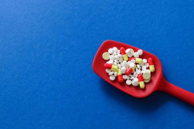 Cuillère rouge avec des pilules, des comprimés et des capsules de médicaments pharmaceutiques avec espace de copie Photo Premium