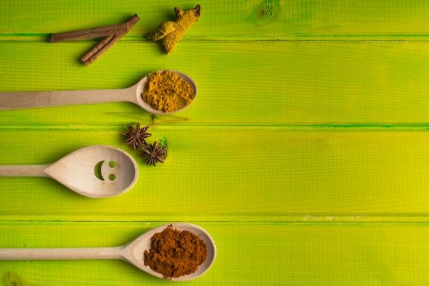 Cuillères et épices sur table verte Photo gratuit