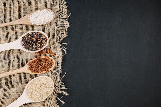 Cuillères avec riz assorti sur toile de lin Photo gratuit