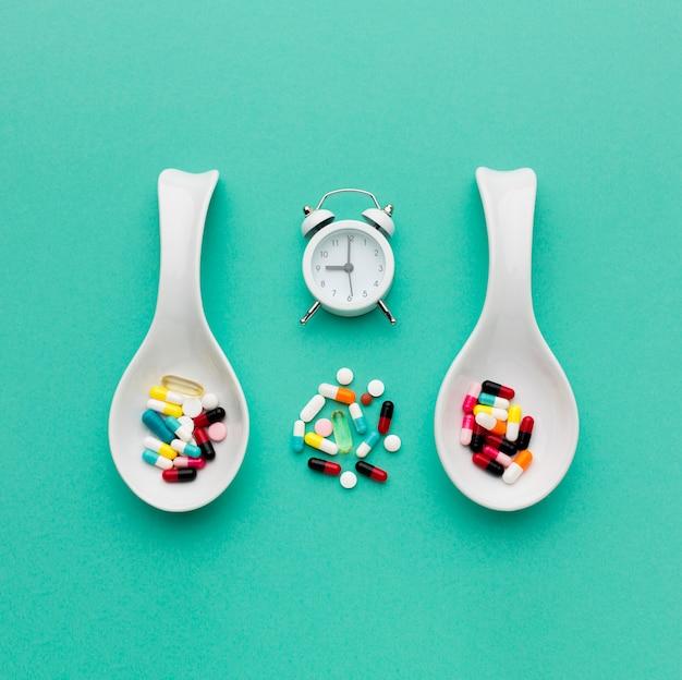 Cuillères Vue De Dessus Avec Pilules Et Horloge Photo gratuit