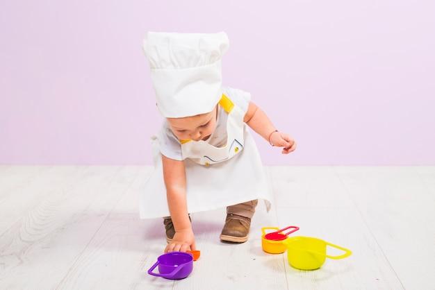 Cuire un enfant jouant avec des plats de jouets Photo gratuit