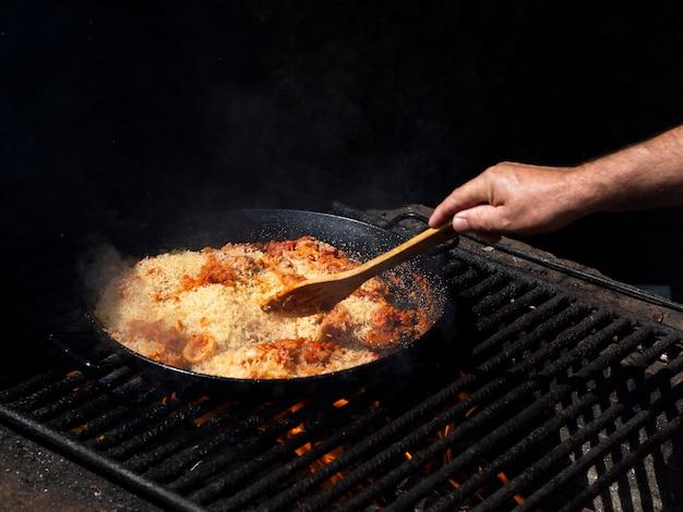 Cuire en mélangeant le riz avec les anneaux de calamars et les légumes sur la poêle Photo gratuit