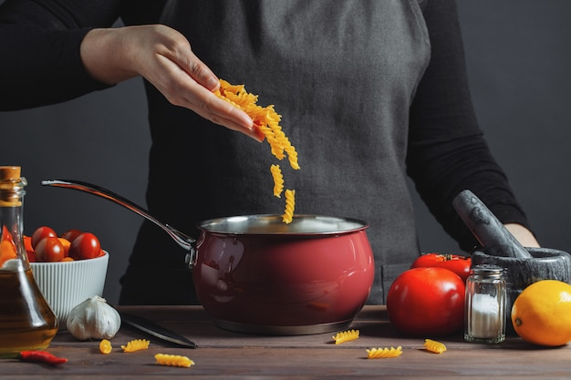 Cuire des pâtes italiennes dans une casserole dans la cuisine. Photo Premium